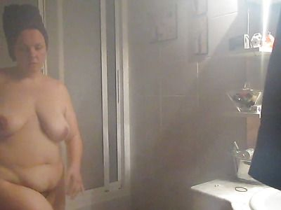 A mature woman takes a hot shower